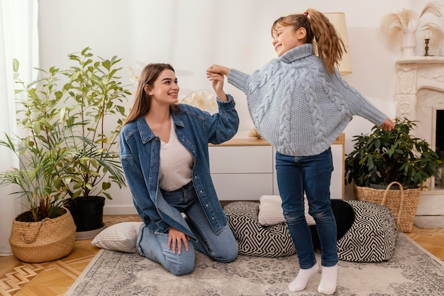 Mother and daughter at home dancing