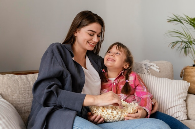 Mother and daughter at home eating popcorn