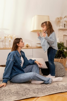 Mother and daughter at home playing
