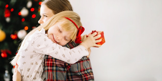 Mother and daughter hugging in front of christmas tree Premium Photo