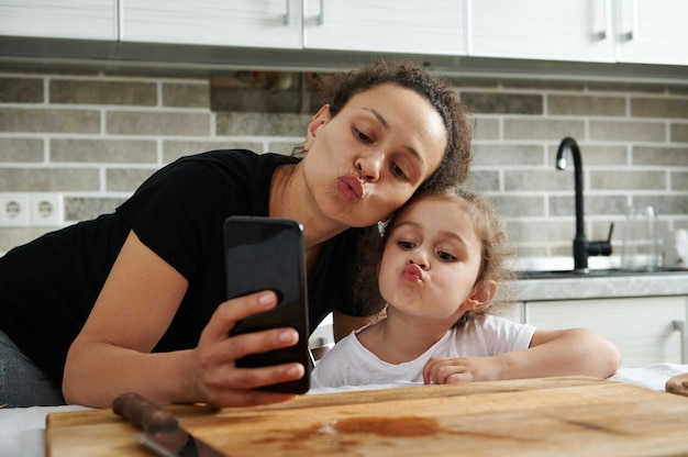 Mother and daughter hugging and looking at the mobile phone camera while taking a selfie in the kitchen while cooking