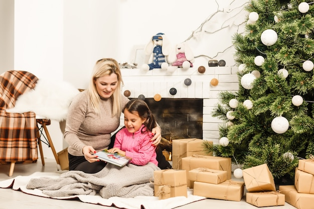 Mother and daughter hugging near christmas tree