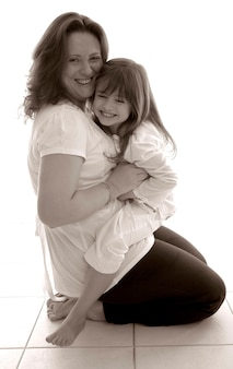 Mother and daughter hugging and smiling, portrait (b&w)