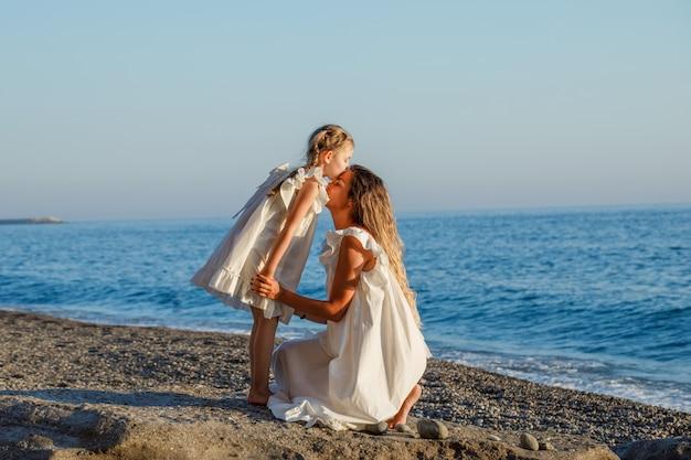 Madre e figlia che abbracciano in abito bianco in riva al mare durante il giorno.