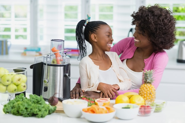 Mother and daughter interacting in kitchen at home