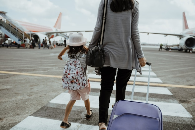 A mother and daughter join hands walking with a suitcase