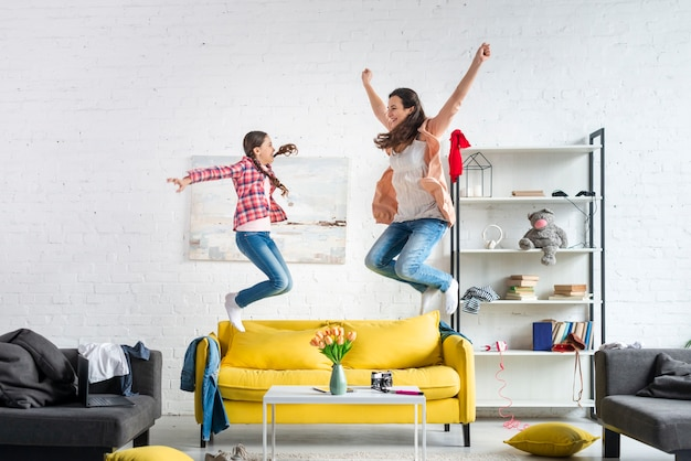 Mother and daughter jumping on the couch
