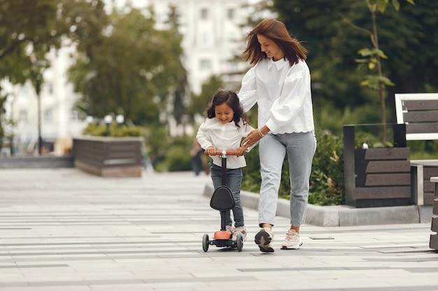 Madre e figlia sul motorino di scossa nel parco. i bambini imparano a pattinare sul roller. bambina che pattina sulla soleggiata giornata estiva.