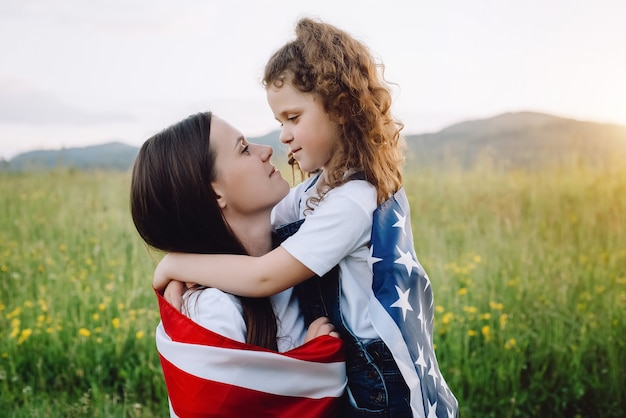 Mother and daughter kid with us flag outdoors