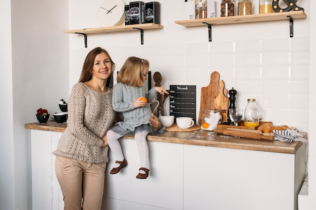 Mother and daughter in kitchen at home.