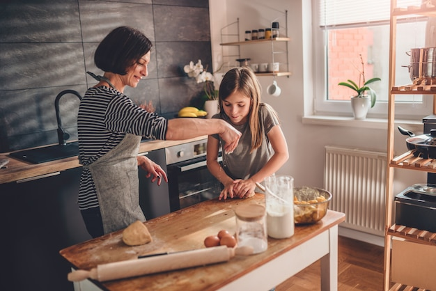 Mother and daughter kneading dough on the wooden table