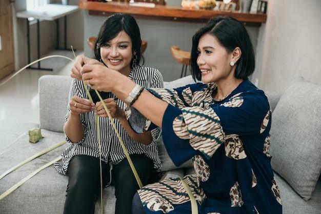 母亲和女儿学习如何制作ketupat的编织包装
