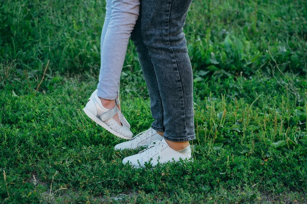 Mother and daughter legs and shoes on the grass, only feet
