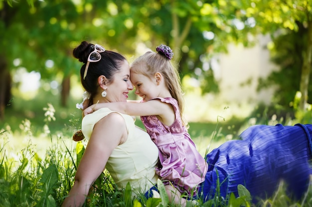 Mother and the daughter look at each other, smile, embrace, sit on a grass in the sunny summer day.