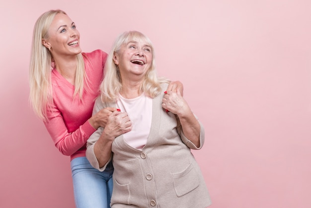 Mother and daughter looking away and copy space background