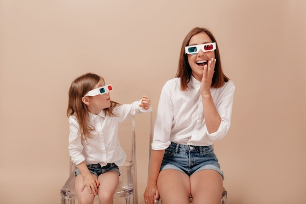 Mother and daughter looking to each other and smiling in 3d glasses to camera on couch isolated on beige background.