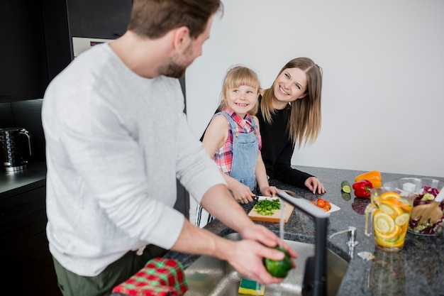 Mother and daughter looking at man washing pepper