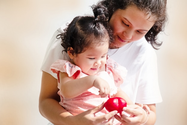 Mother and daughter looking at small red heart in hands