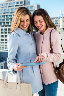 Mother and daughter looking at the tablet and smiling