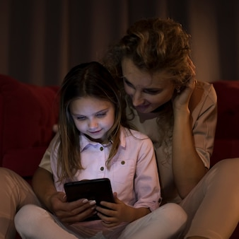 Mother and daughter looking on their tablet