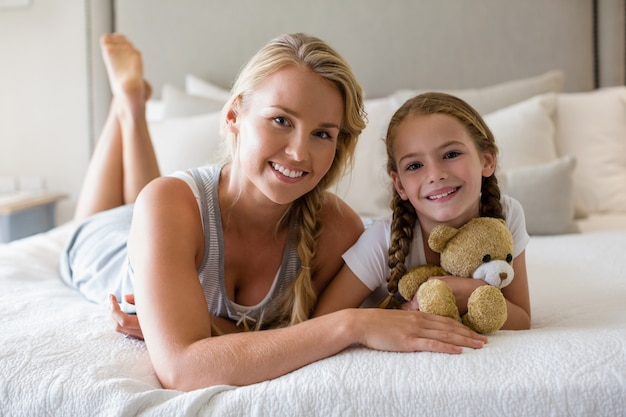 Mother and daughter lying on bed with teddy bear in bedroom