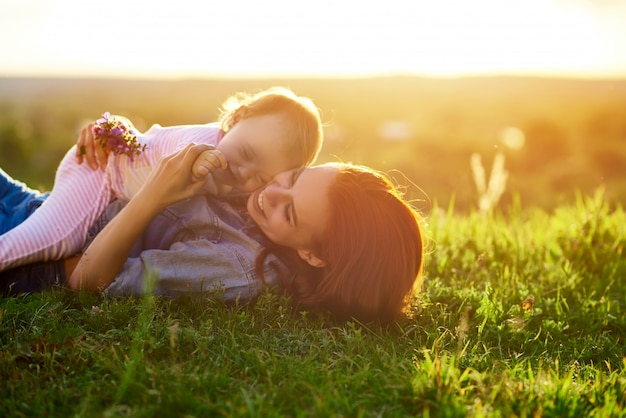 Mother and daughter lying on grass in field while sunset.
