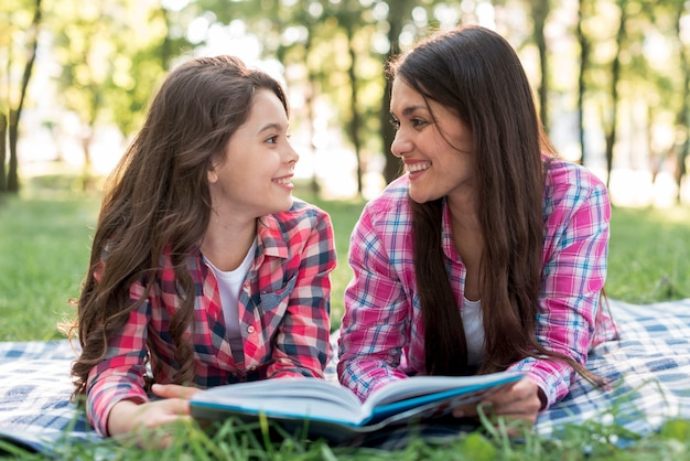 Mother and daughter lying on grass looking at each other while holding book in park