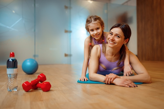 Mother and daughter lying on mat together in gym, fitness workout, gymnastic. mom and little girl in sportswear, joint training in sport club