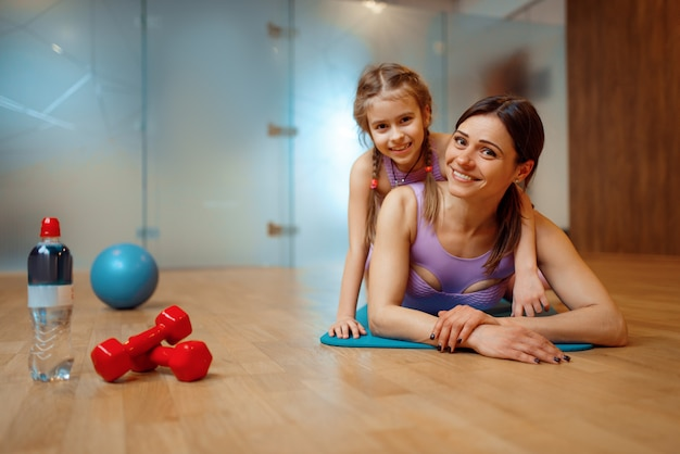 Mother and daughter lying on mat together in gym
