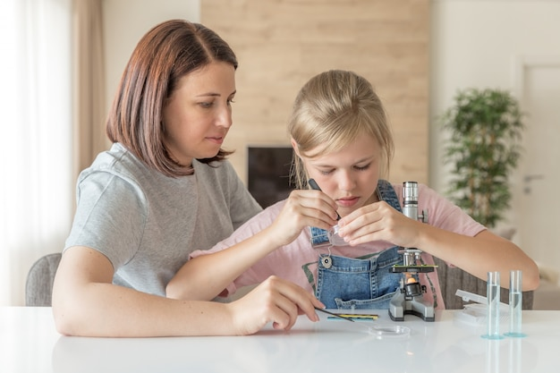 Mother and daughter make chemical experiments with microscope at home