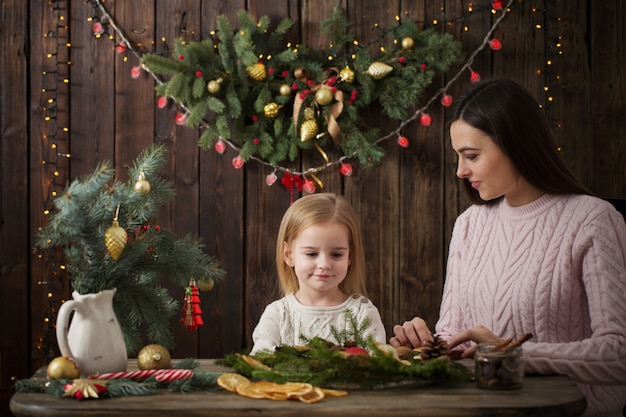 Mother and daughter make  christmas wreath