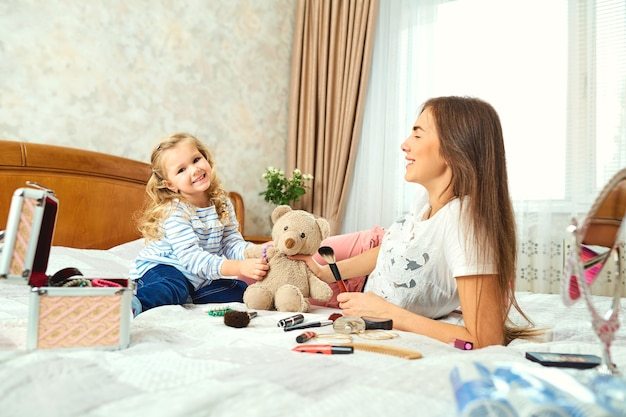 Mother and daughter do make-up, play on the bed by the window.
