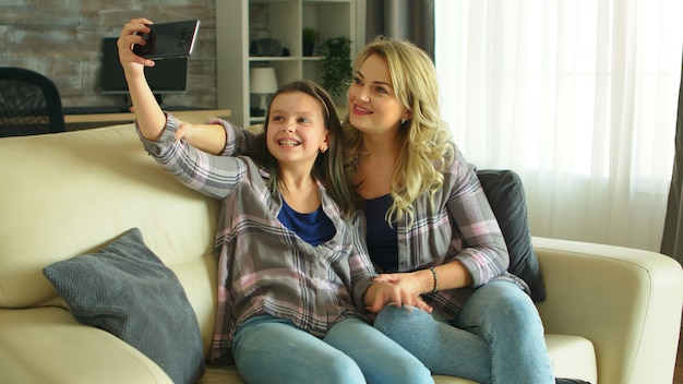 Mother and daughter making funny faces while taking a selfie sitting on the couch in living room.