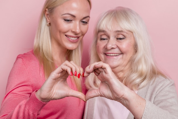 Mother and daughter making a heart shape from hands