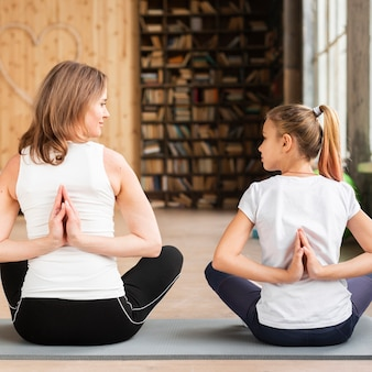 Mother and daughter meditating on yoga mats looking at each other