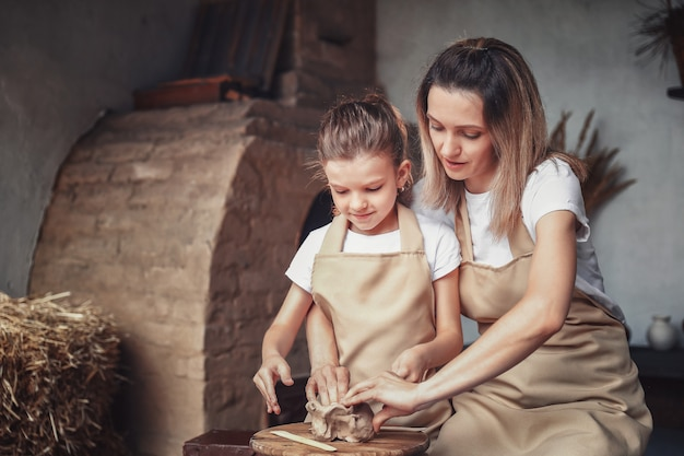 Mother and daughter mold with clay, enjoying pottery art and production process