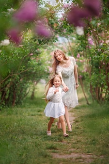 Mother and daughter near a flowering bush, spring, spring family photo shoot
