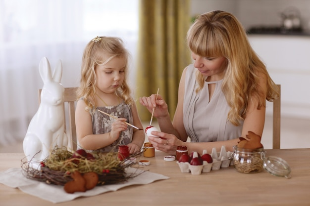 Mother and daughter paint easter eggs in the room at the holiday table.