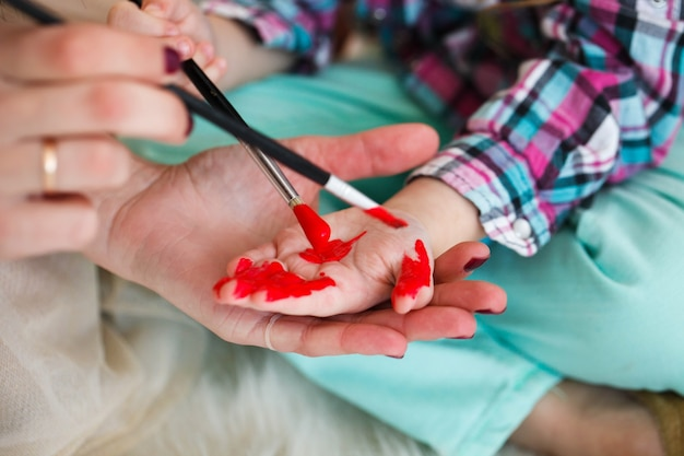 Mother and daughter paint their hands in red color sitting on the floor