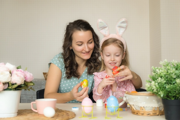 Mother and daughter painting eggs for easter