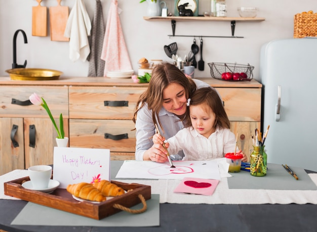 Mother and daughter painting heart at table