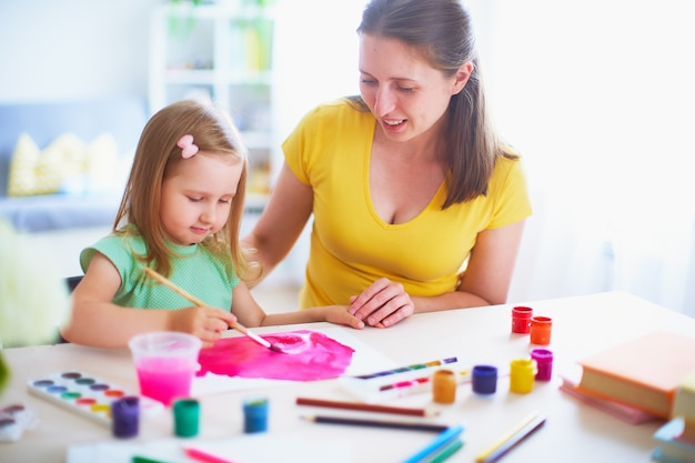 Mother daughter paints watercolor on a sheet of paper sitting at home at the table in a bright room.