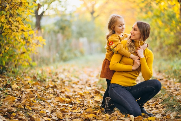 Mother and daughter in park full of leaves