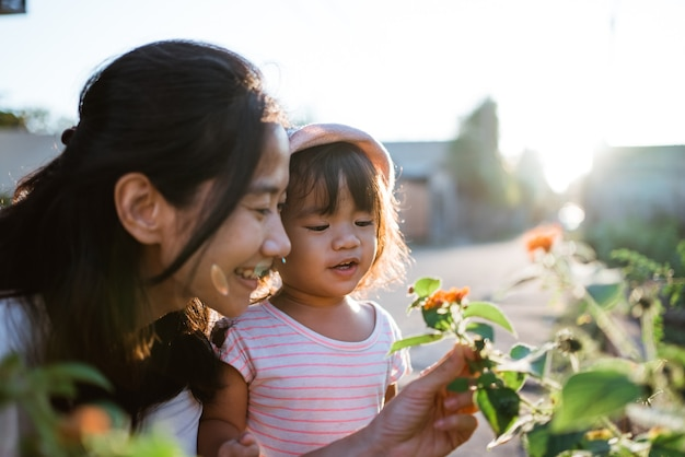 Mother and daughter picking pretty colourful flowes in the park