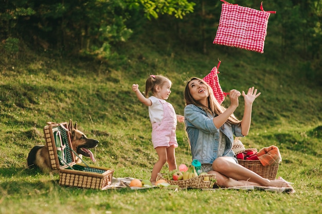 Mother and daughter at a picnic with a dog