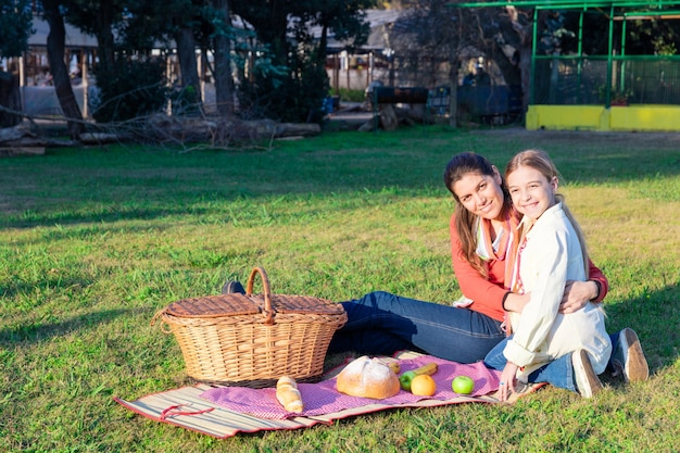 Mother and daughter picnicking in the park