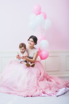 Mother and daughter in pink interior with vintage chair and balloons in beautiful dresses