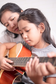 Mother and daughter play the guitar