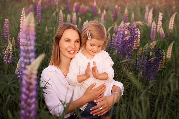 Mother and daughter play together in meadow fields