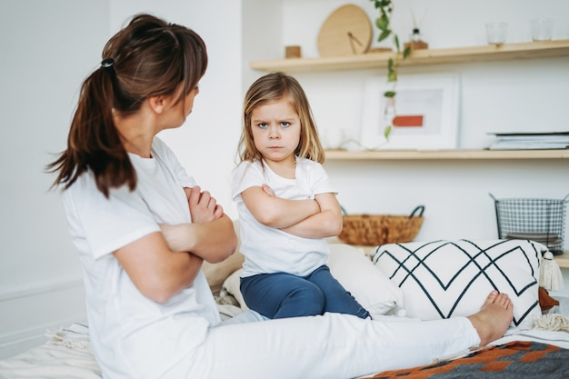 Mother and daughter playing, girl is angry, she lives negative emotions. family on bed at the bright interior